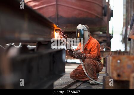 Welder welding girder in shipyard workshop - Stock Photo