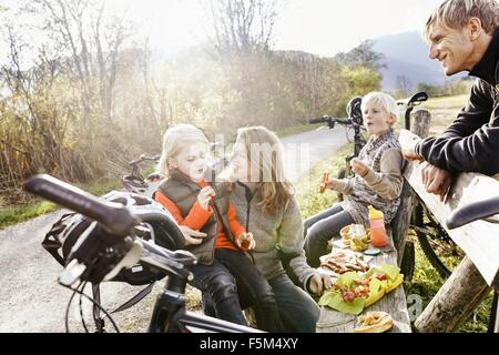 Family with bicycles resting on bench by roadside eating picnic smiling - Stock Photo