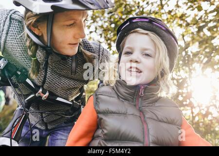 Low angle view of mother and daughter on bicycles wearing helmets looking at camera - Stock Photo