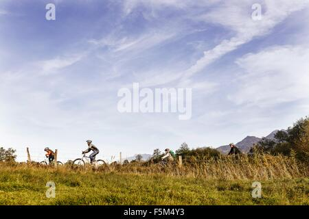 Side view of family riding bicycles on farmland - Stock Photo