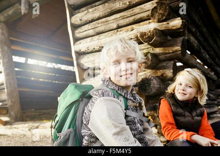 Blonde haired brother and sister sitting outside log cabin looking at camera smiling - Stock Photo
