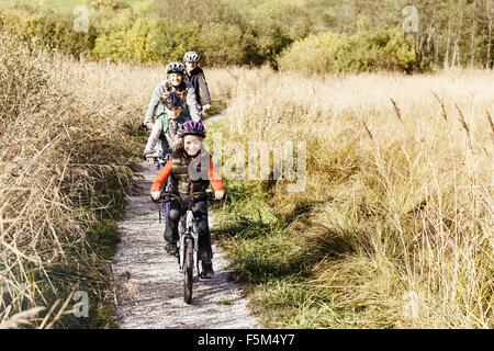 Front view of family cycling on rural path looking at camera smiling