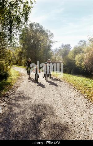 Front view of family on rural road riding bicycles - Stock Photo