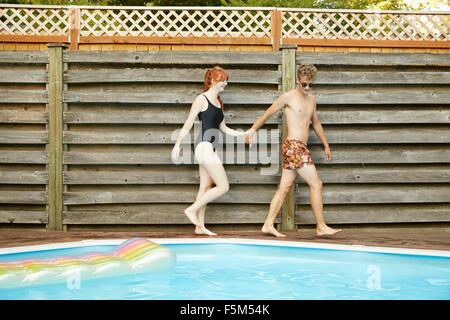 Young couple wearing swimwear holding hands on poolside - Stock Photo