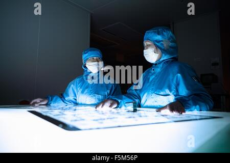 Female workers discussing flex circuit in flexible electronics factory clean room - Stock Photo