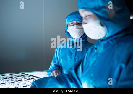 Female workers discussing flex circuit on lightbox in flexible electronics factory clean room - Stock Photo