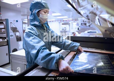 Female worker removing flex circuit from machine in flexible electronics factory clean room - Stock Photo