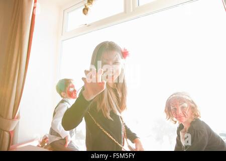 Children in face paint, girl making a growling face - Stock Photo
