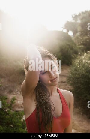 Portrait of sunlit young woman with hands in hair at beach - Stock Photo