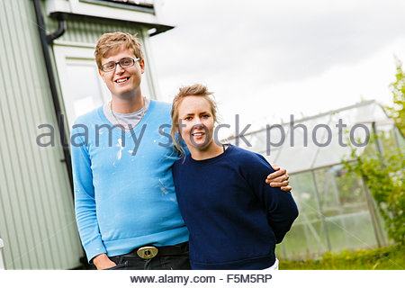 Sweden, Sodermanland, Portrait of young couple with greenhouse in background - Stock Photo