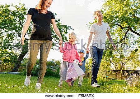 Sweden, Sodermanland, Jarna, Family with two children (12-17 months, 4-5) in garden - Stock Photo