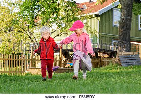Sweden, Sodermanland, Jarna, Children (2-3, 4-5) playing on front yard - Stock Photo