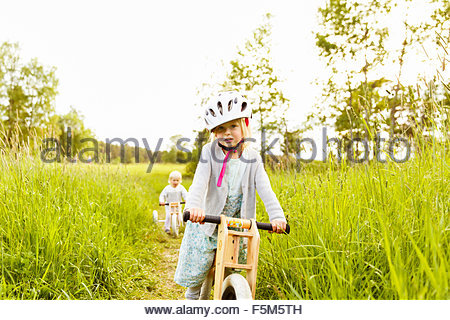 Sweden, Sodermanland, Nacka, Girl (4-5) on bicycle in park and boy (2-3) in background - Stock Photo