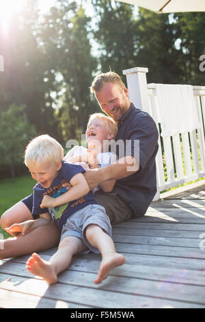 Sweden, Stockholm Archipelago, Grasko, Father playing with sons (4-5, 6-7) outdoors - Stock Photo