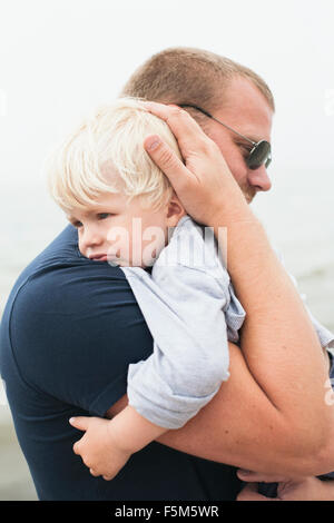 Sweden, Gotland, Ljugarn, Man embracing boy (2-3) - Stock Photo