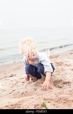 Sweden, Gotland, Ljugarn, Boy (4-5) playing o beach - Stock Photo