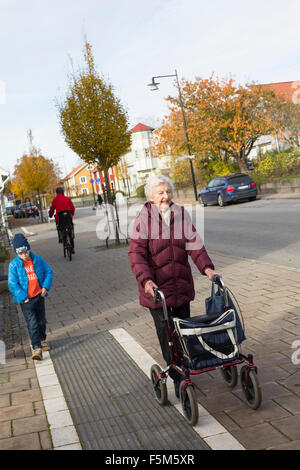 Sweden, Smaland, Tingsryd, Boy (6-7) walking with great-grandmother - Stock Photo
