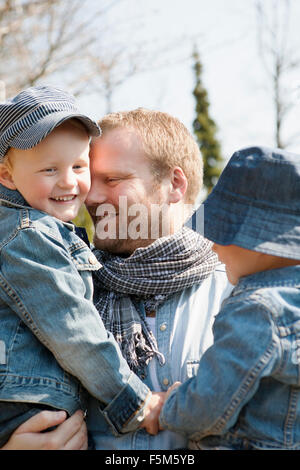 Sweden, Sodermanland, Alvsjo, Father holding sons (4-5, 6-7) - Stock Photo