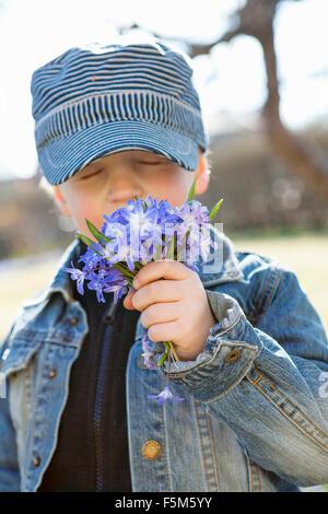 Sweden, Sodermanland, Boy (6-7) smelling flowers - Stock Photo