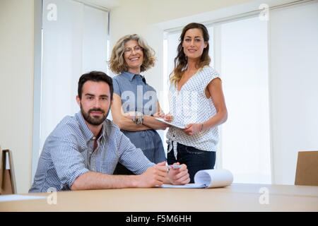 Portrait of businessman and two female colleagues in office - Stock Photo