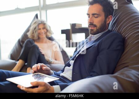 Two designers relaxing on beanbag chairs in office - Stock Photo