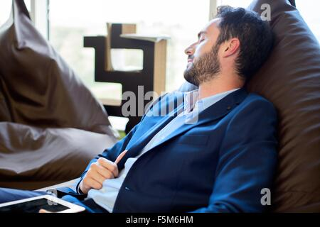 Young male designer sleeping on beanbag chairs in office - Stock Photo