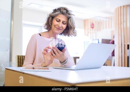 Portrait of senior female designer texting on smartphone in office - Stock Photo
