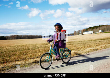 Sweden, Vastra Gotaland, Gullspang, Runnas, Girl (6-7) cycling in countryside - Stock Photo