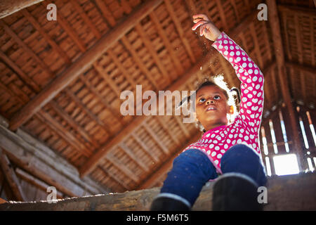 Sweden, Vastra Gotaland, Gullspang, Runnas, Girl (6-7) sitting in barn - Stock Photo