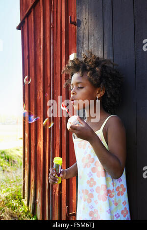 Sweden, Vastra Gotaland, Gullspang, Runnas, Girl (6-7) blowing soap bubbles - Stock Photo