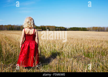 Sweden, Vastra Gotaland, Gullspang, Girl (4-5) wearing red dress standing in field - Stock Photo