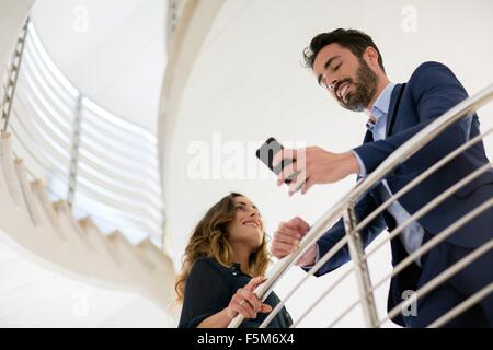Young businessman reading smartphone texts on office stairway - Stock Photo