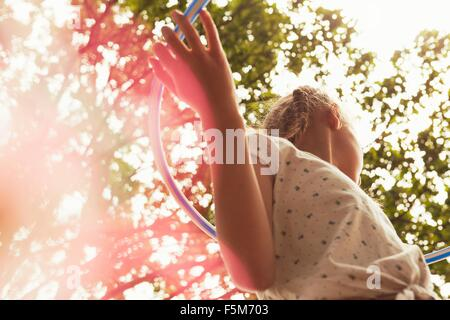 Low angle view of girl playing with hula hoop looking away - Stock Photo