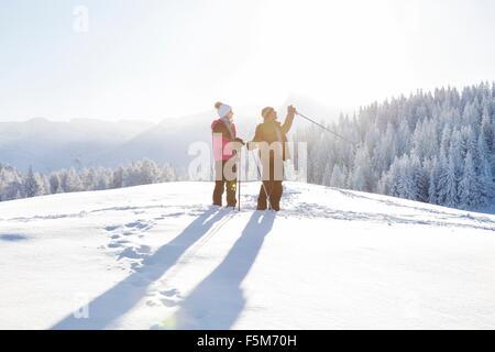 Senior couple on snow covered landscape holding walking poles looking away, Sattelbergalm, Tyrol, Austria - Stock Photo