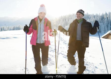 Front view of senior couple on snow covered landscape holding walking poles looking at camera, Sattelbergalm, Tyrol, - Stock Photo