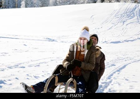 Senior couple sitting on sledge looking at camera smiling, Sattelbergalm, Tyrol, Austria - Stock Photo