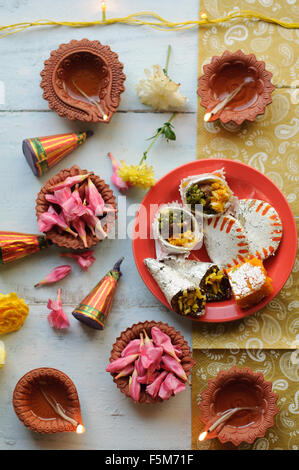 Diwali Diyas on a wooden background with festive flowers and lights - Stock Photo