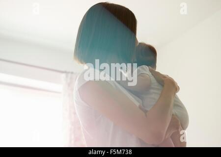 Mother carrying baby in bedroom - Stock Photo