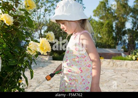 Girl wearing sunhat watering roses - Stock Photo