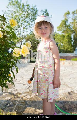 Portrait of girl wearing sunhat watering roses - Stock Photo