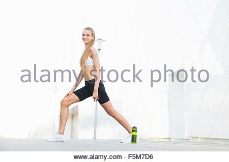 Young female runner warming up on city sidewalk - Stock Photo