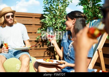 Friends talking and drinking at rooftop party - Stock Photo