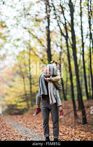 Mother giving daughter piggyback ride in autumn forest - Stock Photo