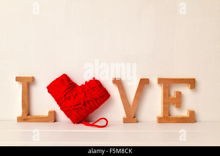 some wooden letters and a heart-shaped coil of red yarn forming the word love - Stock Photo