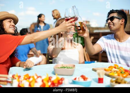 Male and female friends making a toast at rooftop barbecue - Stock Photo