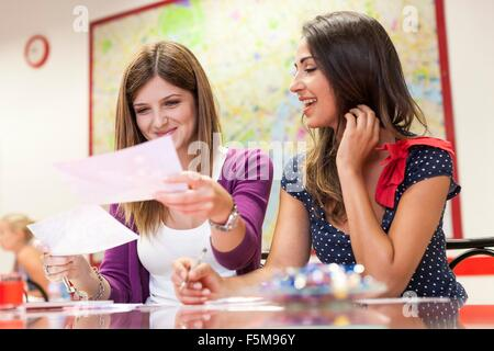 Two young women sitting together, studying - Stock Photo