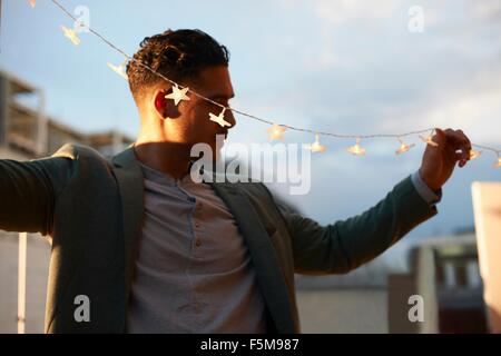 Man handing garden lights for early evening party - Stock Photo