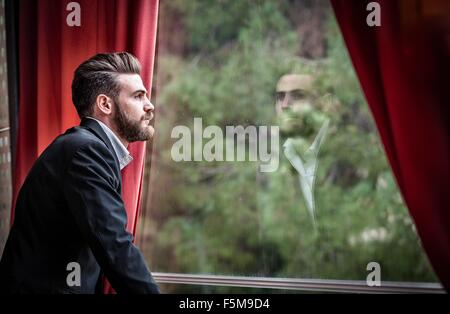 Side view of mid adult man wearing suit looking out of window - Stock Photo
