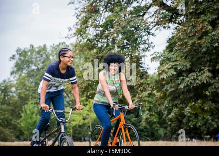 Mother and son riding on bicycles smiling - Stock Photo