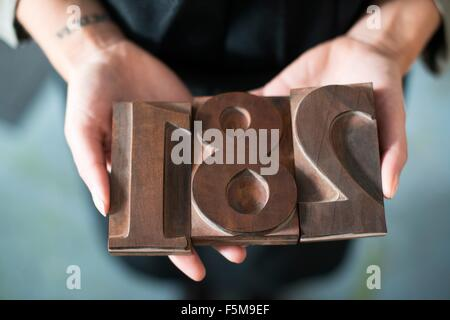 Womans hands holding traditional letterpress numerals workshop - Stock Photo